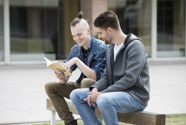 Grafiikassa kaksi miestä lukee kirjaa istuen penkin selkänojalla.
