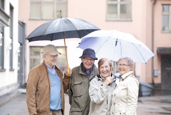 Kaksi miestä ja kaksi naista seisovat sateenvarjojen alla hymyillen